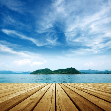 Under the blue sky,platform beside sea . (relax, dock,\ lake)