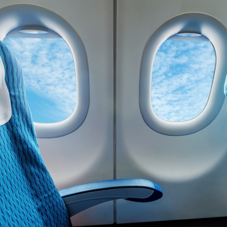 plane window: Empty aircraft seats and windows. Stock Photo