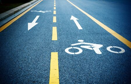 Bike path, dark road and yellow lines  photo