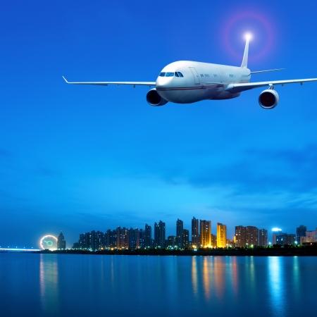 川沿い都市上の夜に航空機。 写真素材