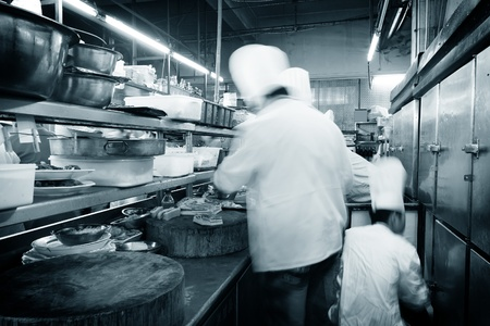 cooking utensils: Crowded kitchen, a narrow aisle, working chef