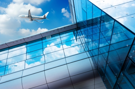 glass curtain wall and aircraft against a blue sky
