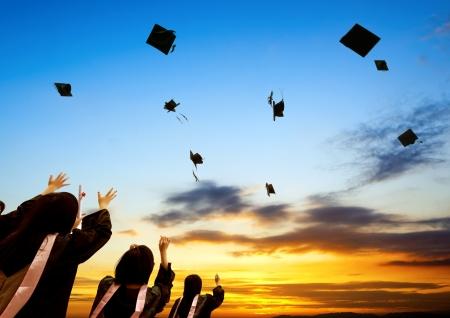 gorros de graduacion: Graduados chinos y el cielo del atardecer. Foto de archivo