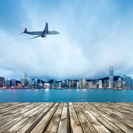 hk: Hong Kongs Victoria Harbour at night. Cloudy sky and airliner. Stock Photo