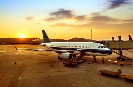 Airplane near the terminal in an airport at the sunset Stock Photo