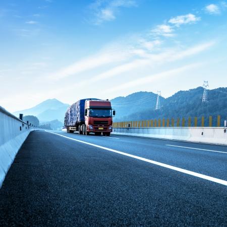 運輸: 紅色卡車在高速公路上高速行駛。 版權商用圖片
