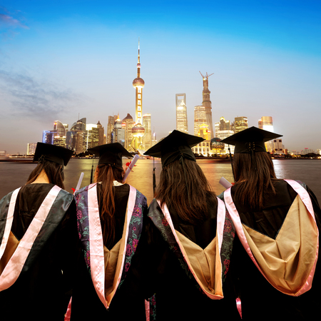 Graduates face skyscrapers in Shanghais Lujiazui financial district.