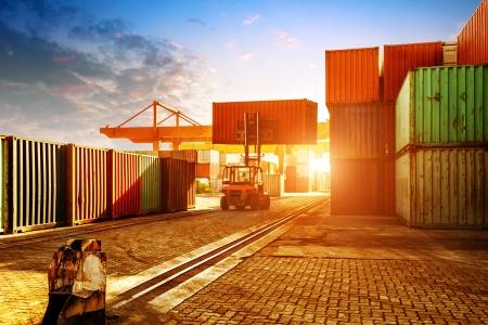 Wenn der Container-Terminal in der Dämmerung, arbeiten Kräne und Gabelstapler.
