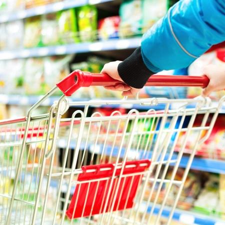 Lady schiebt einen Einkaufswagen im Supermarkt. Standard-Bild