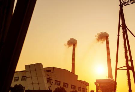 Power plant smokestacks, twilight landscape.