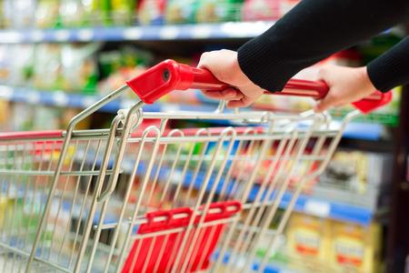 女性はスーパー マーケットでショッピングカートを押します。