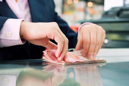 rmb: Female cashier was counting money。 Stock Photo