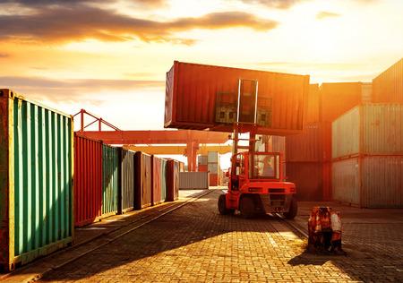 Wenn der Container-Terminal in der Dämmerung, arbeiten Krane und Gabelstapler.