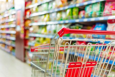 mercearia: Supermercado interior, carrinho de compras vazio vermelho. Banco de Imagens