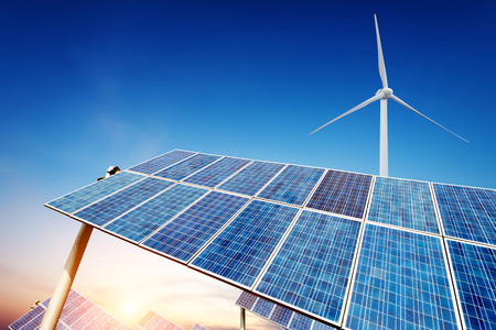 Solar panels and wind turbine against blue sky photo
