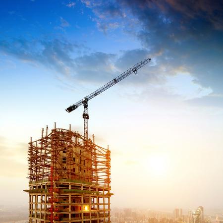 En las obras de construcción anochecer, grandes grúas y ascensores.