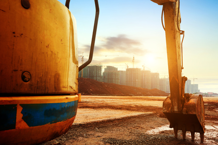 new site: Big excavator on new construction site, in the background the blue sky and sun