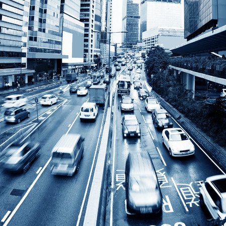 night traffic: Hong Kong street with busy traffic and skyscraper office at dusk. Stock Photo