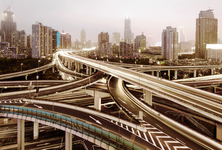 curve road: Freeway in night with cars light in modern city.