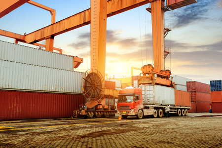 overhead crane: The container terminal at dusk, a large overhead crane and loading trucks.