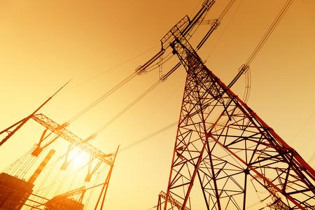 Torre de alta tensión y chimenea de la planta de energía en el fondo del cielo crepuscular