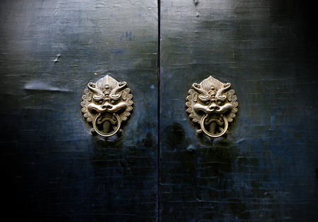door handles: Chinese ancient buildings, mottled and brass door knocker. Stock Photo
