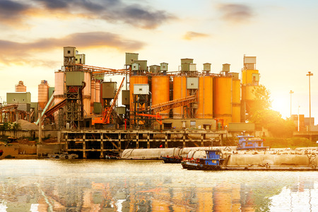 factory building: Riverside cement factory in the evening sky. Stock Photo