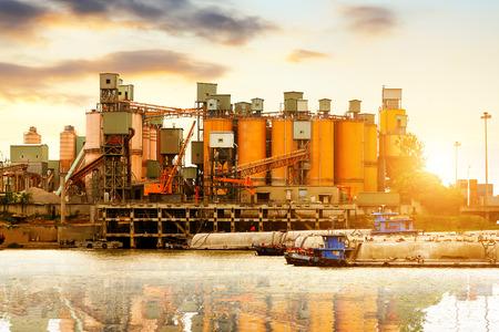 Riverside cement factory in the evening sky. Foto de archivo