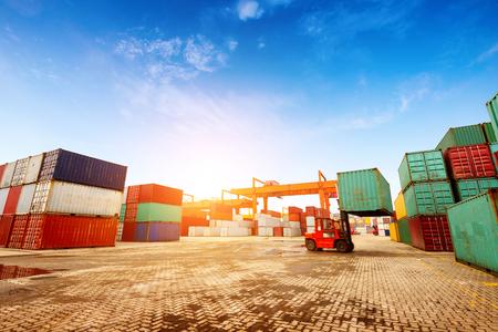 Wanneer de containerterminal in de schemering, werken kranen en heftrucks. Stockfoto
