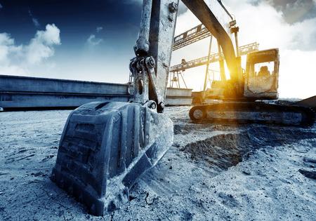 Big Bagger auf neue Baustelle, im Hintergrund der blaue Himmel und Sonne