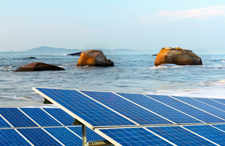 A secluded beach, there are a lot of rocks and solar panels.