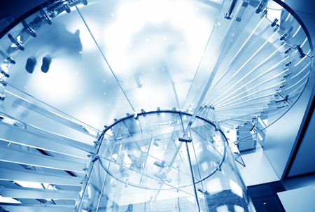 modern glass spiral staircase in shop with motion step photo