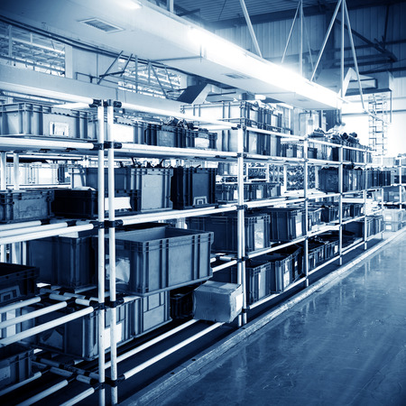 Factory warehouse shelves stocked with plastic containers. Stockfoto