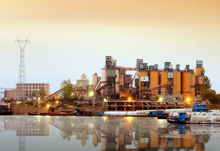 cement chimney: Riverside cement factory in the evening sky. Stock Photo