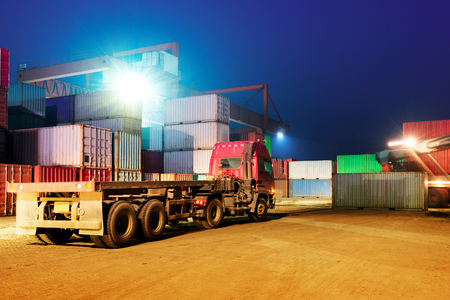 forklifts: Container terminal at night, stopped working forklifts and trucks.