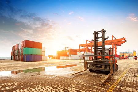 economía: Cuando el terminal de contenedores al atardecer, trabajar gr�as y montacargas. Foto de archivo