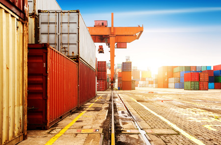 De containerterminal in de schemering, een grote kraan werk.