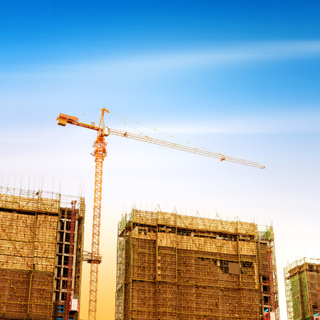 building contractor: Big Construction Site with Working Cranes at dusk for Business