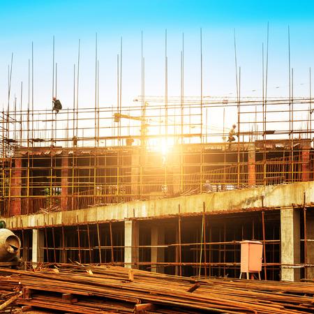 Obra de construcción, los trabajadores y las grúas.