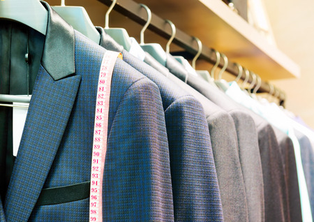 store display: Row of mens suits hanging in closet.
