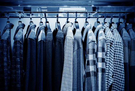 Mens plaid shirts on hangers in a retail store photo