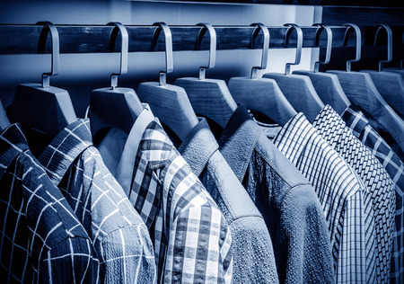 Mens plaid shirts on hangers in a retail store 写真素材
