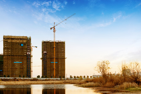 concrete commercial block: Construction site, workers and cranes. Editorial