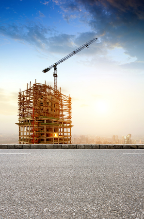 silhouette maison: Grand chantier avec Grues de travail au crépuscule pour les affaires