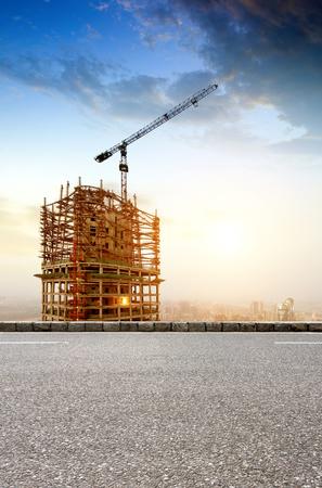 Grote bouwplaats met Werkende Kranen in de schemering voor Business Redactioneel