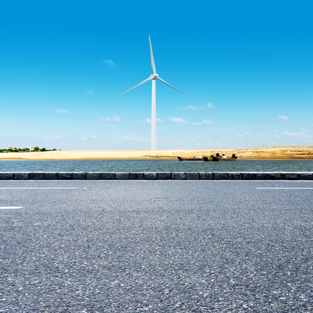 onshore: Wind turbines in green landscape beside a road against blue sky, alternative energy, new natural scenery