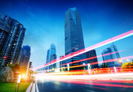 anuncio publicitario: Los senderos de luz en el fondo moderno edificio en Shangai, China.