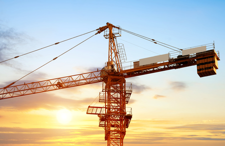 industrial building: Industrial construction cranes and building silhouettes over sun at sunrise.