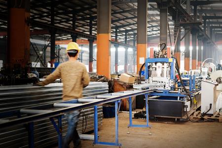 Acciaio catena di montaggio della fabbrica, i lavoratori nel prossimo attrezzature di stampaggio.