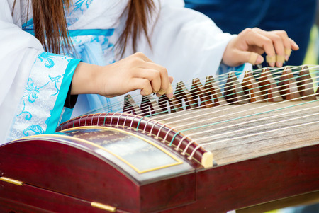 A girl is playing Guzheng.The guzheng or gu zheng, also simply called zheng, is a Chinese plucked zither. It has 18 or more strings and movable bridges.